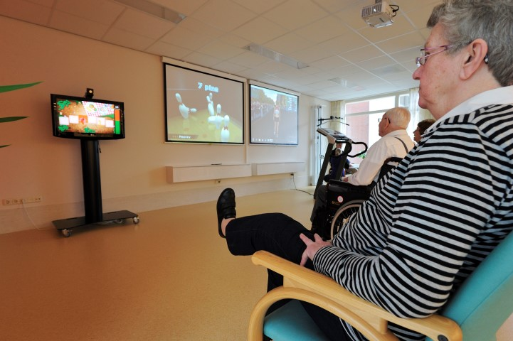 Een cliënt traint haar functie van de knie met het spel Picknick op de SilverFit 3D.