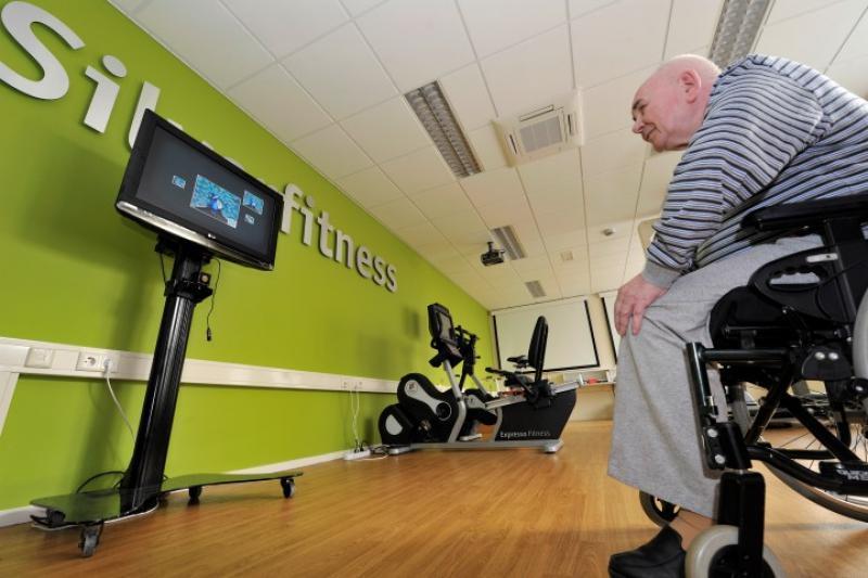 Deze deelnemer traint in een rolstoel. De SilverFit 3D kan gebruikt worden met verschillende hulpmiddelen, bijvoorbeeld een kruk of rollator.