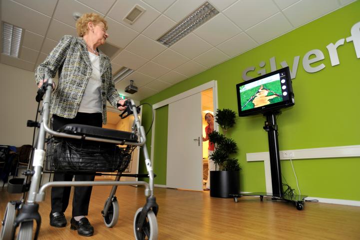 Cliënt doet haar oefeningen met een rollator. De SilverFit 3D kan gebruikt worden met verschillende hulpmiddelen, bijvoorbeeld een rollator, kruk, vierpoot of rolstoel.